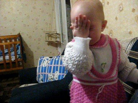 малышка кушает лук и корчит личико